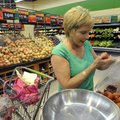 Connie White of Rogers selects tomatoes from the produce area at Walmart Neighborhood Market while s...