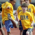 Shaw Elementary fifth-grader Felipe Nava, 11, left, passes the baton to teammate Matthew Burgin, 10,...