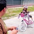 Raymond Gomez watches as his helmeted and padded daughter Angelina Gomez, 7, tries braking and dismo...