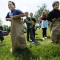 Luis Hernandez, left, and Lim Lee compete Wednesday in a gunny sack race at Cane Hill College. Fourt...
