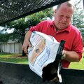 Benny Duncan loads charcoal into a grill Sunday at Rogers Christian Church. Duncan was preparing to ...