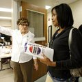 Adrienne Richard of Bentonville is guided Monday to an open station by election official Nancy McClo...