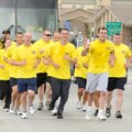 Bentonville police officers near the end of their six-mile run carrying the Flame of Hope Torch thro...
