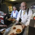 TO SERVE MAN - Collis Geren, right, keeps up with orders of baked beans Thursday during the Universi...