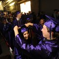 Fayetteville High School senior Dylan Holland, right, helps Huntley Hudgins with her mortar board Th...