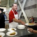 University of Arkansas Chancellor G. David Gearhart serves tacos to staff members Thursday at Donald...