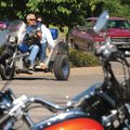 John and Lynn Ayres of Rogers ride their homemade trike Saturday into the parking lot of the Northwe...