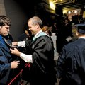 Jay Gilstrap, a drafting teacher at Rogers Heritage High School, right, helps graduating senior Came...