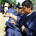 Jesus Pulido writes his name on his mortarboard Saturday while waiting for Har-Ber's commencement. P...