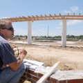 Superintendent Jim Thurman checks elevations of sidewalks Friday at Orchards Park in Bentonville. Th...