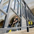 Kelly Paulk sweeps the stairway to the Benton County Courthouse in Bentonville on Monday. An auction...