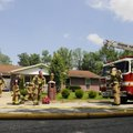 Rogers firefighters respond to a house fire at 503 S. 19th St. in Rogers on Monday. The house is own...