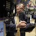 Trader Kenneth Polcari, left, uses a phone post on the floor of the New York Stock Exchange on Tuesd...
