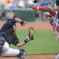 Northwest Arkansas catcher Manny Pina holds onto the ball for an out after colliding with Arkansas b...