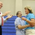 Virginia Mocivnik, center, hugs long-time friend Brenda Alexander as Mark Kruger, assistant principa...