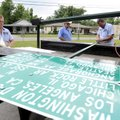 Eric Carter, right, signs and marking technician, trims a pole Tuesday as Troy Lewis, left, signs an...
