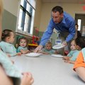 Paul Stone, senior vice president of Sam's Club West Division, hands out plates to children Wednesda...