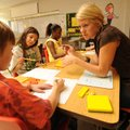 Adrienne Seeger, a second-grade teacher at Leverett Elementary School, helps Skyler Blickenstaff, le...