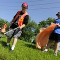 Gilbert Howell, left, and Katie Henderson work together to pick up trash Friday along Southeast 10t...