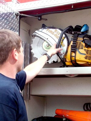 Capt. Brian Johnson shows the new circular saw which can cut either metal or wood.