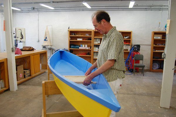 john-van-orman-positions-the-traditional-seat-for-the-pirogue-he-made-during-the-boat-building-class-he-taught-at-the-arkansas-craft-school-in-mountain-view-van-orman-chose-to-paint-his-flat-bottom-boat-yellow-and-blue-which-depicts-the-colors-in-the-flag-of-ukraine-the-yellowgold-color-represents-the-fertile-golden-fields-and-the-blue-represents-the-sky-van-orman-spent-two-summers-in-the-ukraine-studying-its-traditional-music