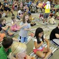 BOOKS AND BEYOND - Jordan Griggs, 6, center, plays along Thursday with the music of Hey Lolly Produc...