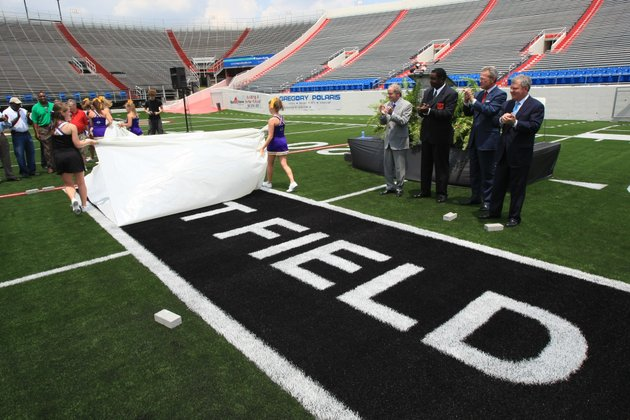 cheerleaders-from-mount-st-marys-and-catholic-high-school-take-the-cover-of-a-logo-on-the-field-wednesday-at-war-memorial-stadium-during-a-press-conference-to-announce-a-sponsorship-naming-the-playing-surface-the-att-field-making-the-announcement-were-background-left-to-right-att-arkansas-state-president-ed-drilling-arkansas-veterans-commission-chairman-terry-williams-att-vice-president-and-general-manager-steve-gray-and-war-memorial-stadium-commission-chairman-gary-smith