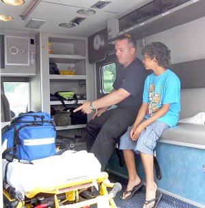 NEBCO emergency medical technician Jamie Baggett showed off the workings inside a NEBCO ambulance to Danny Berkvens during the open house Saturday, June 26, at the new Station 2 on Posy Mountain Road in Garfield. Danny is the son of Clarice and Pieter Berkvens, new residents of the Lost Bridge Village community, which is served by NEBCO Station 2.