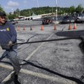 Billy Baker of Springdale sprays a coat of sealant Wednesday on a parking lot at Evelyn Hills Shoppi...