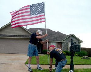 Flags flying in neighborhoods around town are erected by members of the Pea Ridge Optimist Club. Members Bill and Faye Ryan, brothers, placed this flag in Standing Oaks subdivision recently.