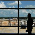 A waiting passenger looks out the window Friday afternoon at construction to expand the terminal at ...