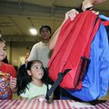 Adrian Becerra, from left, and his sisters Daniella and Fernanda receive their new backpacks Monday ...