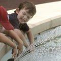 Charlie Sagely, 5, left, and Hudson Tarp, 3, cool off Monday in the fountain on the Bentonville squa...