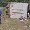 The driver of a tractor-trailer rig carrying garbage fills out an accident report Monday after the t...