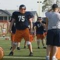 Rogers Heritage offensive lineman Bill Couch, center, listens to a coach before starting a drill dur...