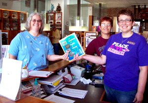 Sheila Hart, left, receives a book of her choice after winning the drawing from names of survey participants. She is pictured with Angela Nelson and Holly Hill. While visiting the library, Hart, the daughter of library volunteer Lenora McClary, filled out the library survey and entered the drawing for a free book of her choice. Her name was drawn and she chose the book The Amphibians and Reptiles of Arkansas because she has been finding copperhead snakes in her yard and she wanted to learn more about them. Hart has lived in Gentry all her life and for the past seven years has worked at Gentry Primary School cafeteria. During her summer breaks she is often here on Monday morning to visit with her mother and to offer her assistance when needed.