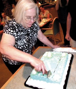 JoAnne Hall cuts her cake at a retirement party held last week in Bella Vista. Hall taught and served as a librarian in the Decatur School District for 33 years.