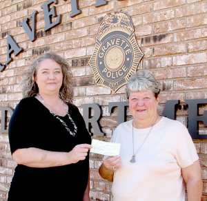 Pennie Barry who oversees the adoption process for pets at the Gravette Animal Shelter, receives a check from the Jolly Good Times Club to help with operation of the shelter. A fund drive is underway to secure a heating system for the facility.