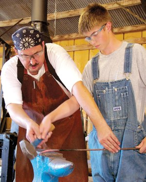 R.J. Barnica, 12, takes a lesson from master blacksmith Dale Custer in the blacksmith shop at the Tired Iron of the Ozarks show grounds on Saturday.
