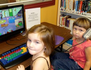 Gracie Robinson and Clara Hoggarth try out the new literacy station at the Gravette Public Library. The new equipment is especially fun for children ages 2 to 10, but adults will find it helpful in learning new languages including Spanish and German.