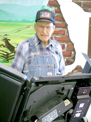 School elections were Tuesday. At left, Russell Walker, 93, a 1937 graduate of Pea Ridge High School, cast his vote.