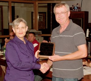 Dianne Burrus receives a Teacher of the Year Award from school board chairman Jim Barnes on Monday night at the high school library.