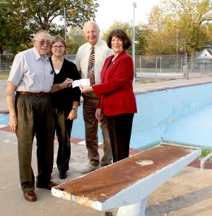Gravette Mayor Bill Howard, left, and Allyson Ransom, Communications and Resource Efficiency Director, stand in front of a missing diving board at the city pool as they accept a $40,000 check from State Senator Kim Hendren and State Representative Mary Lou Slinkard, a state grant to assist with the pool's repair.