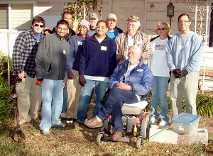 Bart Nelson, Korean War veteran, sits in his wheel chair with the good neighbors who are rebuilding his home. Pictured with Nelson are Chris Mackey, Chet Patel, Shawn Govino, Nick Nagin, Rocky Govino, Jeff Duram, Roger McGovern, Bettie Duram and Byrom Bean.