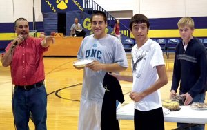 Auctioneer Rob Hopkins took bids on a cream pie with the help of basketball players Taylor Pickup, Bobby Shaw and Evan Owens during the Meet the Bulldogs event on Friday night. The pie auction raised $642 to be used for junior high practice gear, according to coach Donnie Smith. Players were introduced at the event and displayed their skills with scrimmage games and drills.
