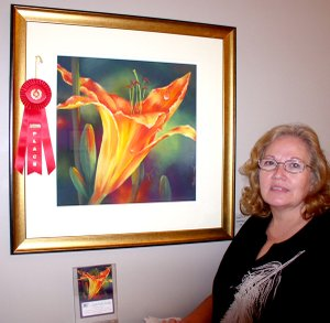 Local artist Susan Edgmon poses with an award-winning painting.