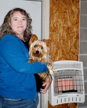 Berry is shown with a Yorkie that was recently picked up in town and has been returned to its owner. The new heating unit is in the background of the photo.