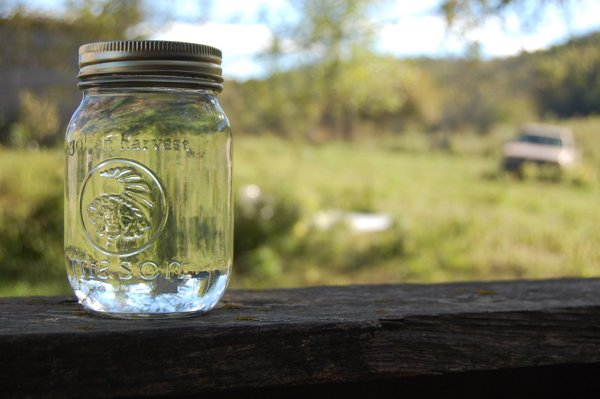 at-the-end-of-a-long-gravel-road-where-a-still-is-hidden-in-a-barn-a-lone-mason-jar-of-fresh-moonshine-sits-atop-a-fence-rail