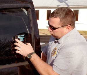 Sgt. Clay Stewart of the Gentry Police Department demonstrates the use of a tint meter on side window glass last week. State law requires front seat side windows to allow a minimum of 25 percent of the light to pass through. Rear side windows must allow 10 percent of light to pass through. Many windows are tinted too dark and restrict vision to the point of causing a driver not to be able to see other traffic or pedestrians.