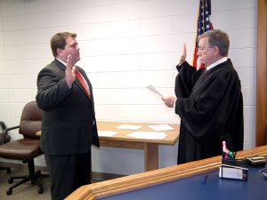 Gravette Mayor Byron Warren takes his oath of office before Judge Jay Finch.